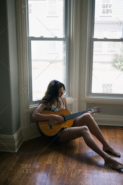 A young woman plays guitar in the corner of a room