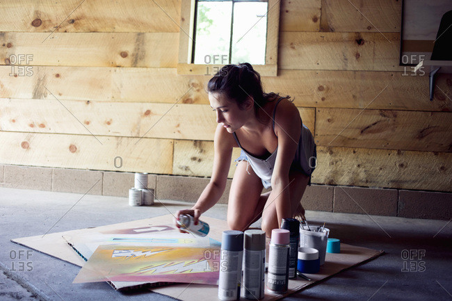 A young woman spray paints a stencil in a workshop