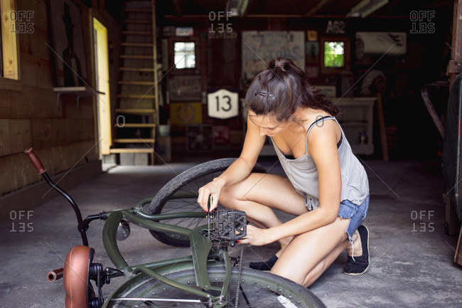 A young woman repairs her bike in a garage