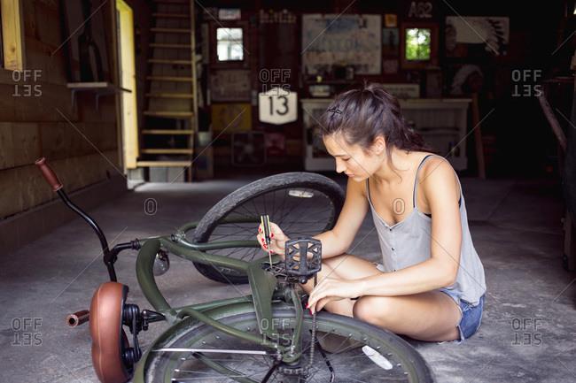 A woman repairs her bike in a garage