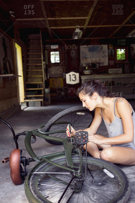 A young woman fixes her bike in a garage