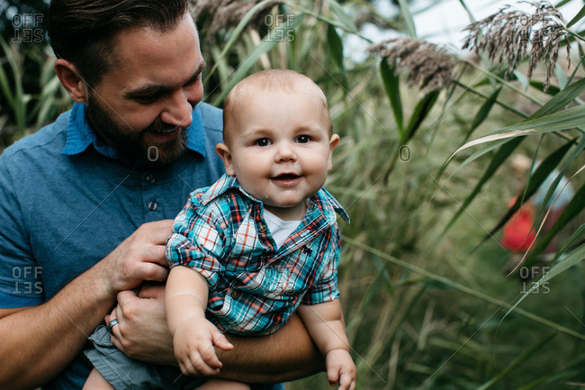 Man holding drooling baby in field of tall grass