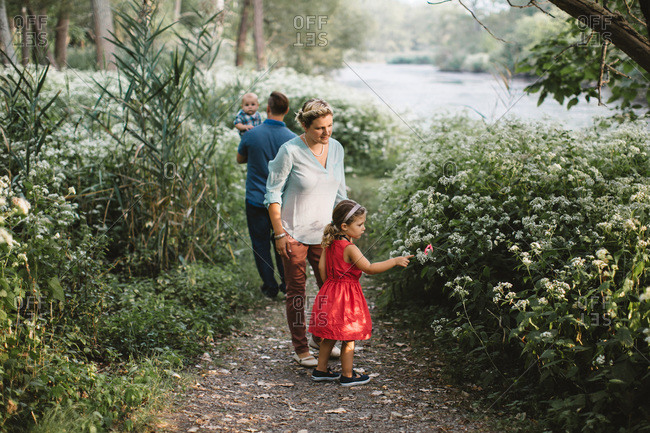 Parents and two young children walk on path through field of wildflowers