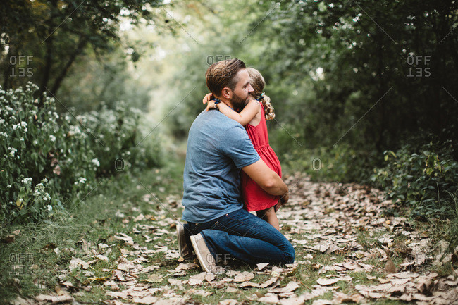 Girl hugging father on forest path