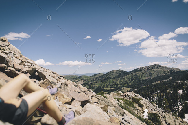 A woman's legs are seen as she rests overlooking the mountains