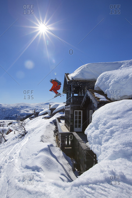 A male freerider in a red suit is jumping from the roof of a wooden building in Myrkdalen