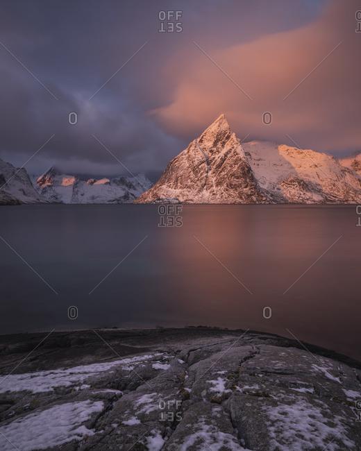 Olstind mountain peak glows pink at sunrise, Toppoy, Moskenesoy, Lofoten Islands, Norway