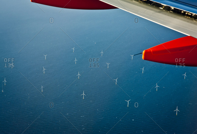 A view of windmills in the ocean from an airplane window