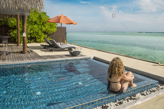 A woman sits next to an oceanfront pool in the Maldives