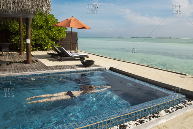 A woman swims in an oceanfront pool in the Maldives