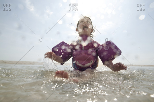 A young girl in floaties splashes in the water at the beach