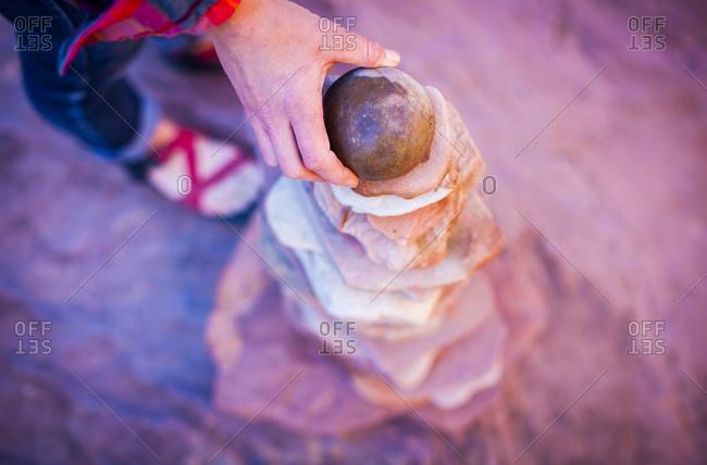 A woman building a sandstone carin