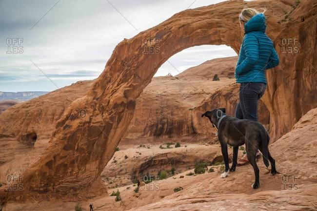 A woman and her dog looking out at Corona Arch, Moab, Utah
