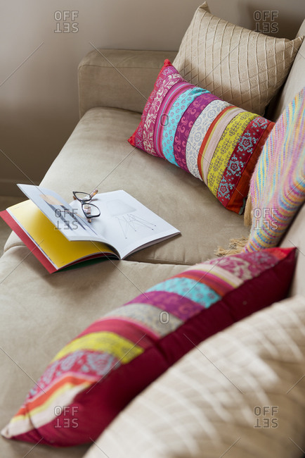 Glasses and book on couch with throw pillows