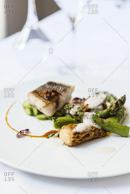 Cod filet and asparagus on a white plate
