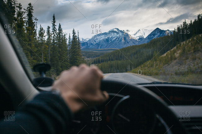A man drives towards Banff National Park in Canada