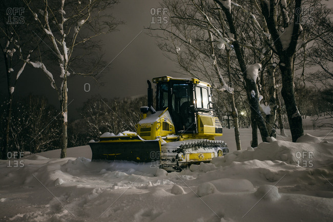 Empty snow plow parked in snow between trees