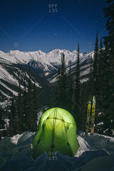 Illuminated tent at a campsite overlooking snow-covered mountains