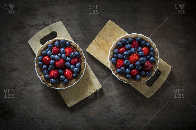 Berry tartlets in baking dishes on wooden boards