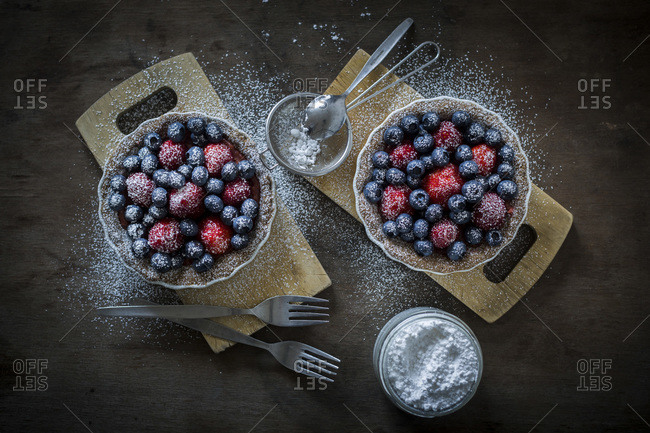 Berry tartlets in baking dishes with powdered sugar