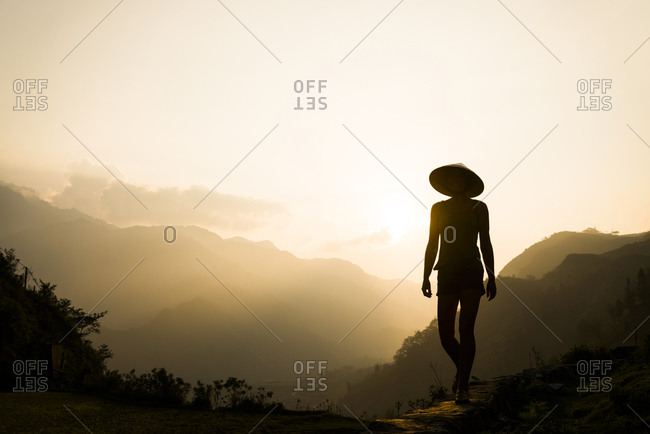 A western female tourist walking on a path in the Sapa Mountains of Northern Vietnam