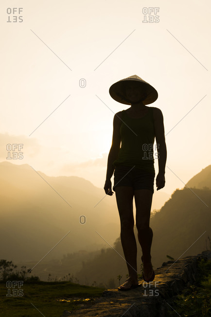 A western female tourist walking a path in the Sapa Mountains of Northern Vietnam