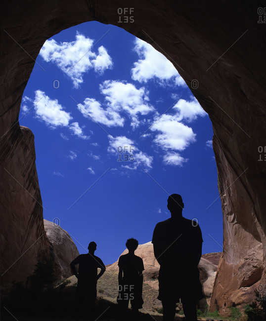 People standing in an arched cave entrance looking at the sky