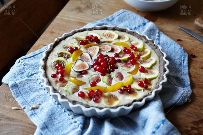 Fig and hazelnut cr�me tart with buckwheat crust on wooden cutting board