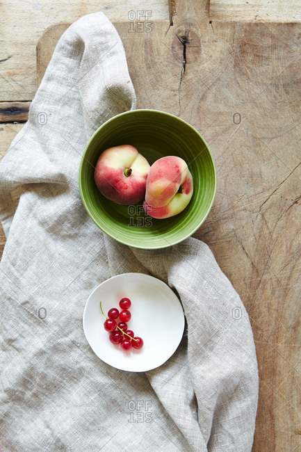 Bowls of peaches and currents arranged on a linen cloth on wooden cutting board