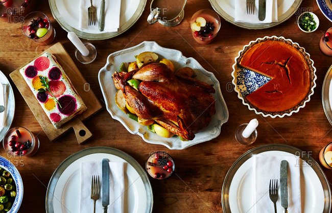 Overhead view of a Thanksgiving dinner table with roasted turkey