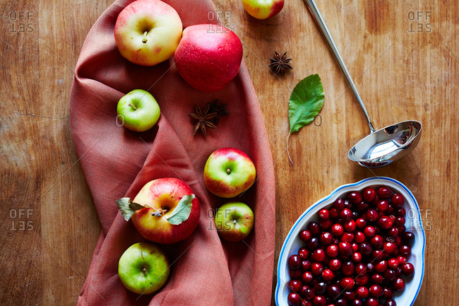 Arrangement of fresh apples, dish of cranberries and star anise on wood background