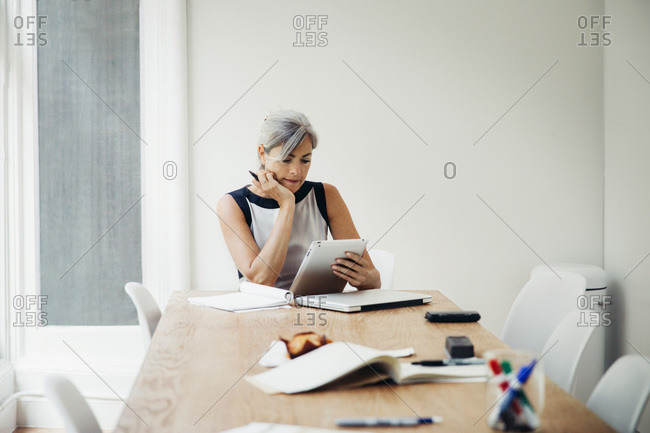 Woman pondering while looking at tablet in office