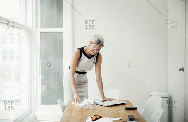 Woman in office looking at notebook and smiling