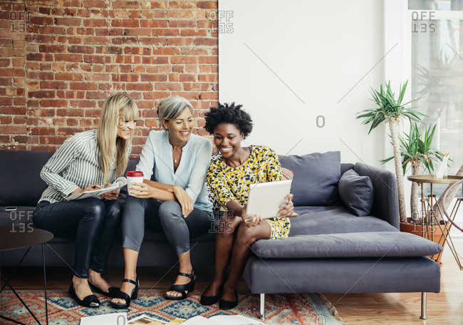 Three woman collaborating on office couch