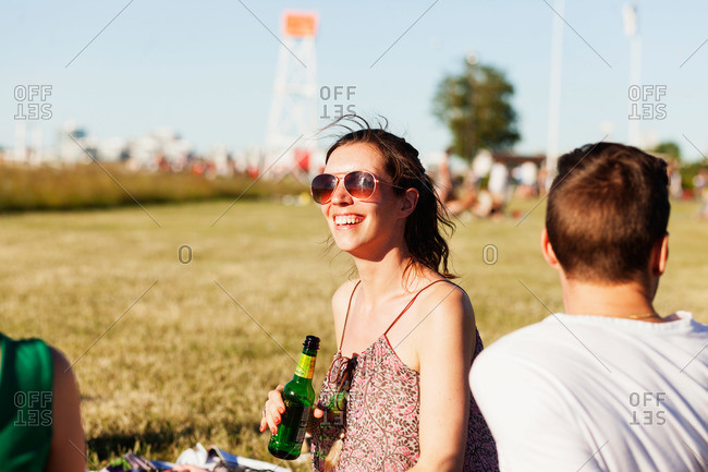 A woman smiles while she sits on a grass at a festival
