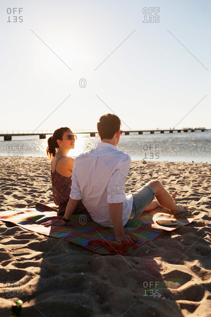 A young couple relaxes on a beach blanket