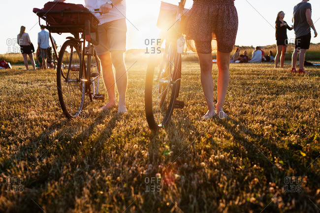 A young couple walking with their bicycles across a field at a picnic