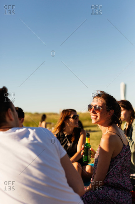Friends smile and laugh at a picnic