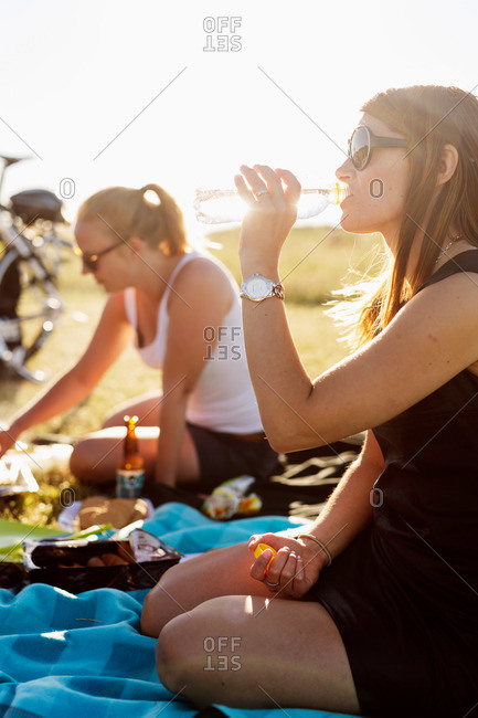 A woman drinks bottled water at picnic