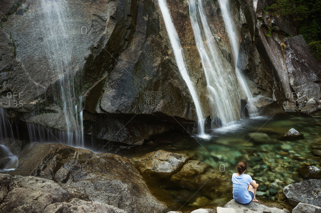 Woman sitting at the base of a waterfall
