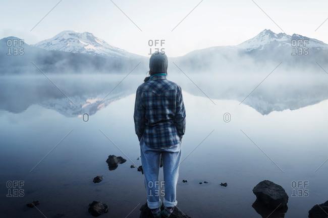 Woman standing at a foggy mountain lake