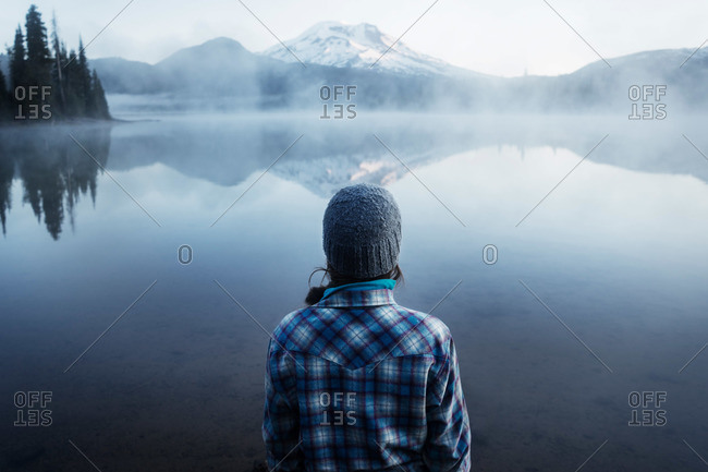 Woman looking at a foggy mountain lake