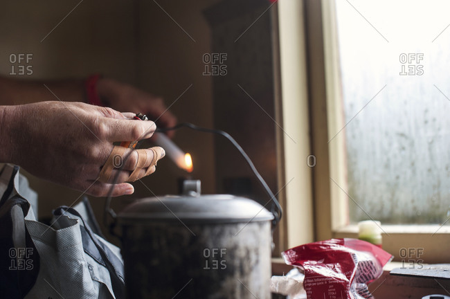 Bandaged hands of man in cabin lighting candles, Nelson Lakes, New Zealand
