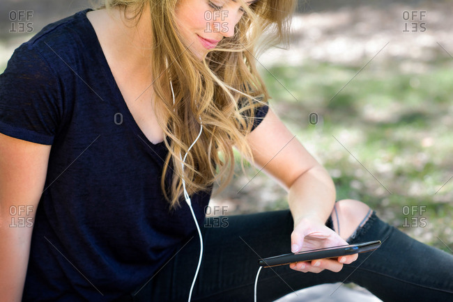 A young woman listens to music on her smartphone
