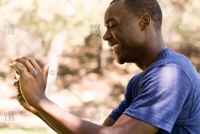 A young man smiles as he takes a photograph in a park