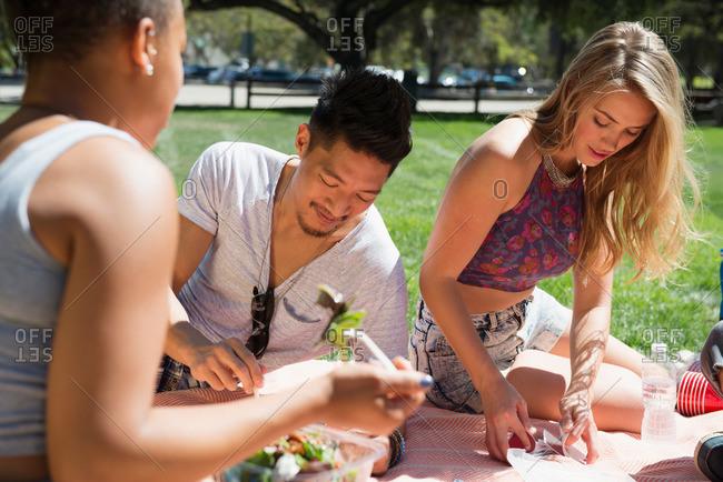 A woman shuffles cards at a picnic