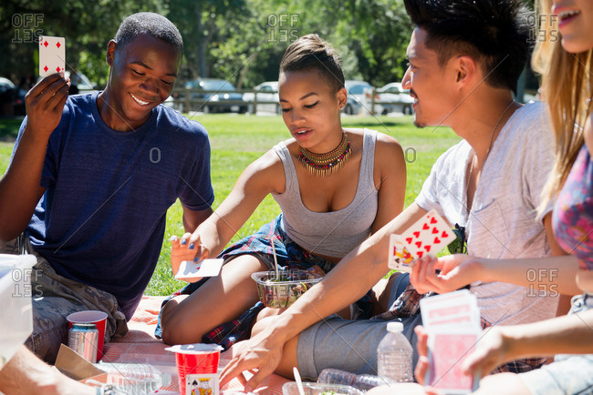 Friends play cards at a picnic