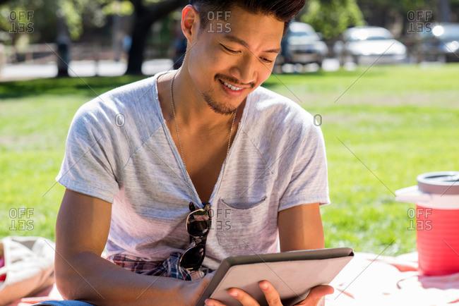 A young man checks his tablet at a picnic