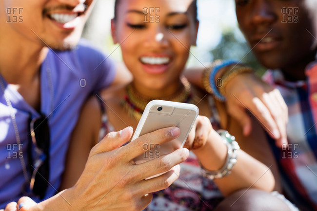 Three friends look at a smartphone together