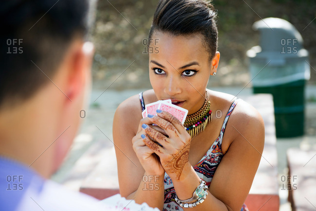 A woman shows her poker face while playing cards